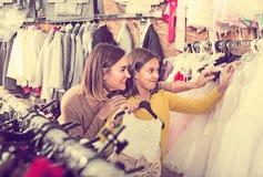 La madre y la hija sonrientes están eligiendo el vestido cómodo Imagen de archivo libre de regalías