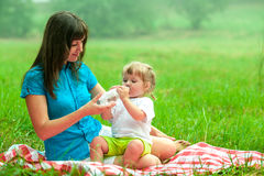 La madre y la hija tienen agua potable de la comida campestre Imagen de archivo libre de regalías