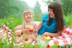 La madre y la hija tienen comida campestre que comen manzanas Foto de archivo