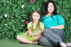La madre y la niña hermosas se sientan en hierba en jardín Foto de archivo