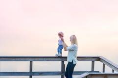La madre y la pequeña hija están en el embarcadero del río Puesta del sol niebla Fotografía de archivo libre de regalías