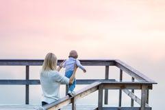 La madre y la pequeña hija están en el embarcadero del río Puesta del sol niebla Imagen de archivo libre de regalías