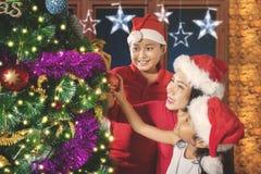 La madre y los niños adornan un árbol de abeto Fotos de archivo libres de regalías