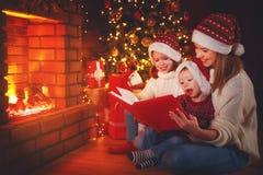 La madre y los niños de la familia leyeron un libro en la Navidad cerca del fuego Foto de archivo