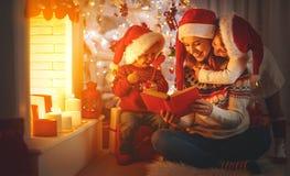 La madre y los niños de la familia leyeron un libro en la Navidad cerca de firep Foto de archivo libre de regalías