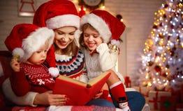 La madre y los niños de la familia leyeron un libro en la Navidad cerca de firep Imágenes de archivo libres de regalías