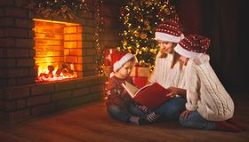 La madre y los niños de la familia leyeron un libro en la Navidad cerca de firep Imagenes de archivo