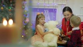 La madre y los niños están considerando un cono del árbol de navidad Regalo de la Navidad cerca del árbol de navidad en casa almacen de metraje de vídeo