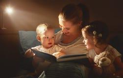La madre y los niños felices de la familia leyeron un libro en cama Fotografía de archivo