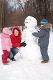 La madre y los niños hacen el muñeco de nieve imagen de archivo