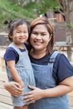 La madre y los niños que llevan vaqueros se adaptan a la cara sonriente con la emoción de la felicidad Fotos de archivo