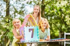 La madre y los niños son felices sobre rompecabezas de la casa ideal Imágenes de archivo libres de regalías