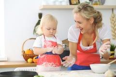 La madre y la pequeña hija están cocinando en la cocina Pasando el tiempo todo junto o concepto de familia feliz Imagen de archivo libre de regalías