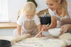 La madre y la pequeña hija están cocinando en la cocina Pasando el tiempo todo junto o concepto de familia feliz Fotos de archivo