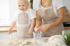 La madre y la pequeña hija están cocinando en la cocina Pasando el tiempo todo junto o concepto de familia feliz Imágenes de archivo libres de regalías
