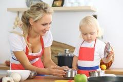 La madre y la pequeña hija están cocinando en la cocina Pasando el tiempo todo junto o concepto de familia feliz Imagenes de archivo