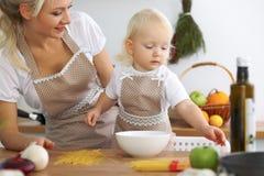 La madre y la pequeña hija están cocinando en la cocina Pasando el tiempo todo junto o concepto de familia feliz Fotografía de archivo