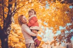 La madre y su bebé se divierten en el parque del otoño fotografía de archivo