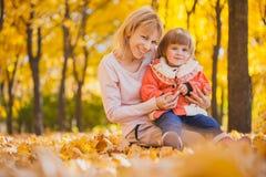 La madre y su bebé se divierten en el parque del otoño imagen de archivo libre de regalías