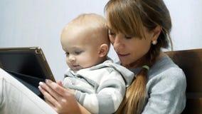 La madre y su hijo miran un vídeo en cama almacen de metraje de vídeo