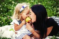 La madre y su niño disfrutan de la primavera temprana, comiendo la manzana, feliz foto de archivo