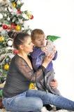 La madre y su pequeño niño se sienta cerca del árbol de navidad con el juguete Fotos de archivo libres de regalías