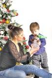 La madre y su pequeño niño se sienta cerca del árbol de navidad con el juguete Imagen de archivo libre de regalías