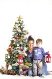 La madre y su pequeño niño se sienta cerca del árbol de navidad con las lámparas rojas Fotografía de archivo