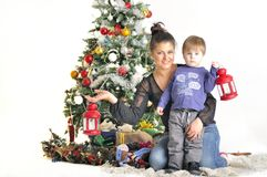La madre y su pequeño niño se sienta cerca del árbol de navidad con las lámparas rojas Imagen de archivo libre de regalías
