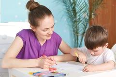 La madre y sus cinco años de la pintura del hijo con los marcadores coloutful en el papel, tienen interés al arte, actitud junto  Foto de archivo libre de regalías