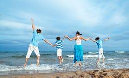 La madre y tres hijos están saltando en la playa Imagenes de archivo