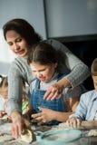 La madre y tres niños preparan algo de la pasta Foto de archivo libre de regalías