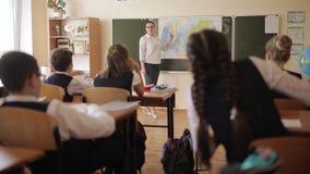La maestra en clase cerca del mapa del mundo comunica con los estudiantes, hace preguntas y las explica almacen de metraje de vídeo