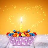 La magdalena adornada del cumpleaños con una encendió la vela y Imágenes de archivo libres de regalías