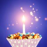 La magdalena adornada del cumpleaños con una encendió la vela y los caramelos coloridos en fondo amarillo Tarjeta de felicitación Foto de archivo libre de regalías