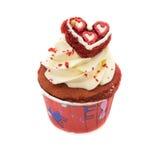 La magdalena del chocolate adornada con la formación de hielo roja del corazón y asperja imagen de archivo