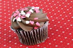 La magdalena del chocolate con el corazón asperja Foto de archivo libre de regalías