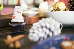 La magdalena hecha en casa de la Navidad adorna como el muñeco de nieve en la tabla Imagen de archivo