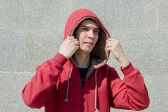 La maglia con cappuccio del tipo in rosso e fa una pausa la parete e guarda al lato immagini stock libere da diritti