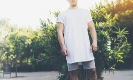 La maglietta in bianco bianca d'uso e gli shorts dell'uomo muscolare barbuto della foto nell'ora legale vacation Parco verde del  Fotografie Stock Libere da Diritti