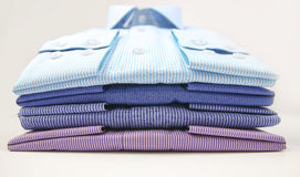 La maglietta degli uomini piegata su fondo Immagini Stock