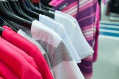 La maglietta delle donne sul gancio nel deposito Fotografie Stock Libere da Diritti