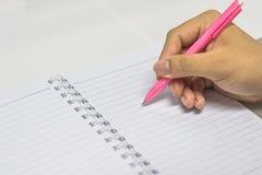La main écrivent sur le cahier Image libre de droits