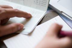 La main écrivent sur le carnet avec l'intérêt des textes avec la banque de compte huent photo libre de droits