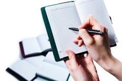 La main écrivent sur le carnet sur le fond blanc Image stock
