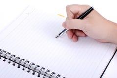 La main écrivent sur un carnet Images libres de droits