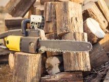 La main électrique a vu et couper des arbres pour le bois de chauffage Photo stock
