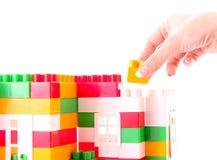 La main ajoutent la brique de jouet à la construction de jouet photos libres de droits