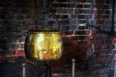 La main 1590 antique simple de chaudron de vintage forgée faisant cuire le pot hangged par d'or de cheminée de foyer le vieux image stock