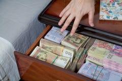 La main atteint pour l'argent dans la table de chevet Photographie stock libre de droits